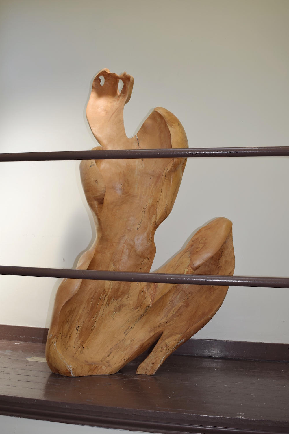 side shot of large wooden sculpture of abstract female form